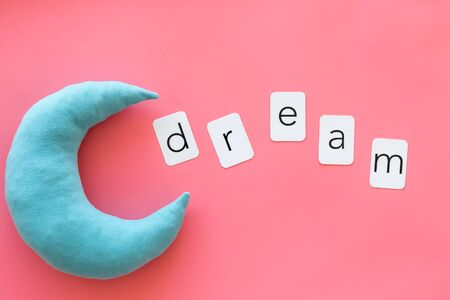 Go to bed. Dream word and moon for sleep concept on pink background top view