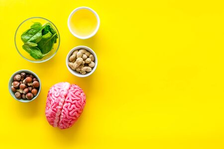 Snacks for mind. Brain food concept with peanut, hazelnut, seed-oil, spinage on yellow background top view copyspace