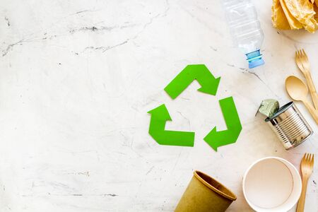 Green recycling symbol and different garbage, paper cup, plastic bottle, flatware, can for ecology on marble background top view mock up
