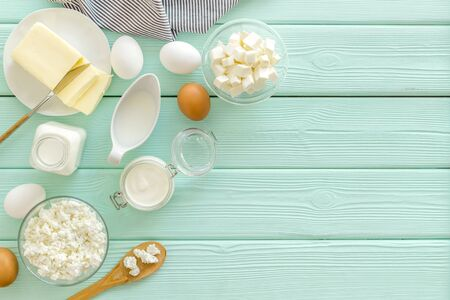Farm products. Fresh dairy products for breakfast with milk, cottage, eggs, yogurt on mint green wooden background top view mock up