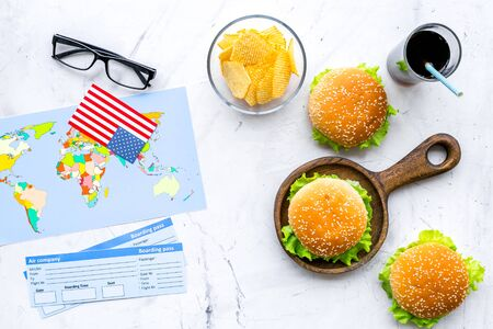 Gastronomical tourism concept with American flag, passport, tickets, map, glasses and food symbols, burgers, chips, drink on marble background top view
