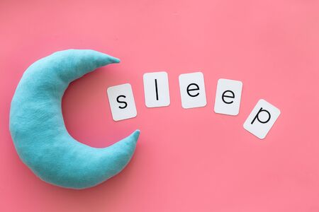 Go to bed. Sleep word and help yourself to fall asleep concept on pink background top view