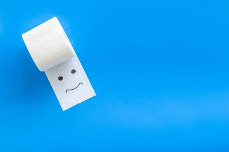 Disease of colon. Proctology concept with toilet paper roll and painted face on blue background top view mock up Stock Photo