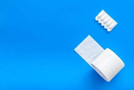 Disease of colon. Proctology concept with toilet paper roll and rectal suppository on blue background top view mock up Stock Photo
