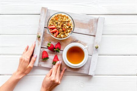 Breakfast in bed with granola, tea and fruit on tray on white wooden background top view