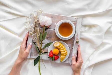 Breakfast in bed with flower, tea and fruit on tray in hands on white bed background top view