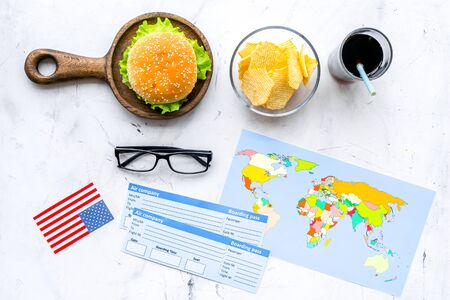 Traditional food. Burger, chips, map, tickets and USA flag for gastronomical tourism to America on marble background top view