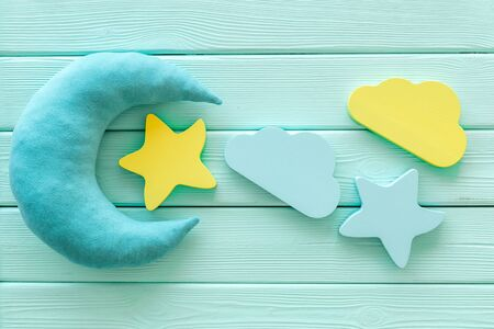 Good dreams. Night sleep concept with moon, clouds, stars toys on mint green wooden background top view 版權商用圖片