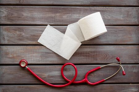 Disease of colon. Toilet paper roll and stethoscope for proctology diseases concept on wooden background top view