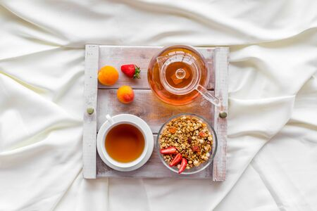 Homemade breakfast in bed with granola, tea in pot and cup on tray on white bed background top view