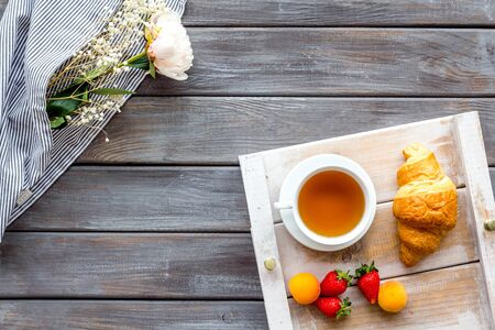 Homemade breakfast in bed with croissant, tea and fruit on tray on wooden background top view Stock Photo