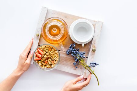 Homemade breakfast in bed with granola, tea in pot and cup on tray on white background top view