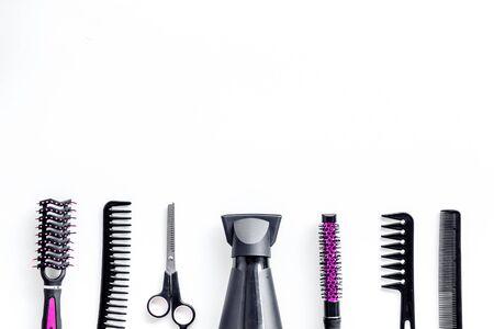 Notion de coupe de cheveux. Accessoires roses professionnels de coiffeur sur le bureau de travail fond blanc vue de dessus copyspace Banque d'images