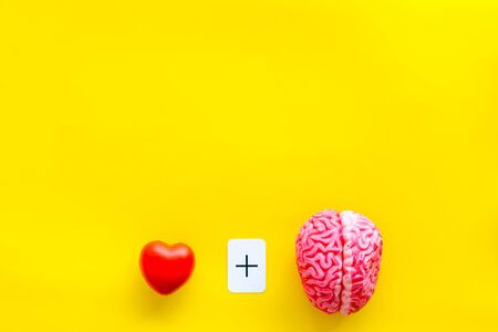 Feelings and mind concept with brain plus heart on yellow background top view mock up.