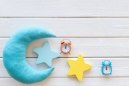Night sleep concept with moon and clouds toys and alarm clock on white wooden background top view mock-up