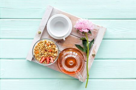 Breakfast in bed with granola, tea in pot and cup on tray on mint green wooden background top view