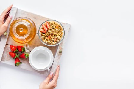 Breakfast in bed with granola, tea in pot and cup on tray on white background top view