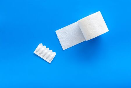 Disease of colon concept with toilet paper roll and rectal suppository on blue background top view