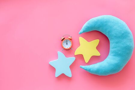 Good dreams. Night sleep concept with moon and clouds toys and alarm clock on pink background top view 版權商用圖片
