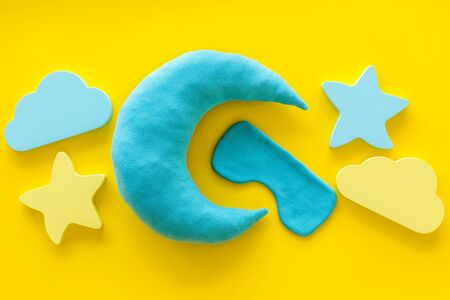 Good dreams. Night sleep concept with moon, clouds, stars toys and blindfold on yellow background top view 版權商用圖片