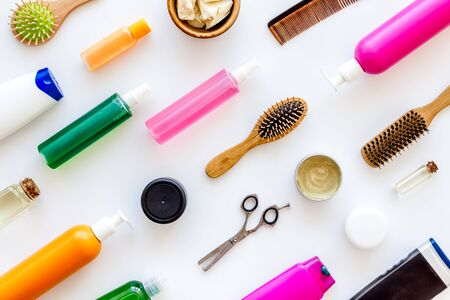 Homemade spa. Cosmetics for hair care with jojoba, argan or coconut oil, scissors, comb and shampoo in bottle on white background top view pattern