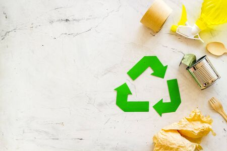 Green recycling symbol and different garbage for ecology on marble background top view Stock Photo