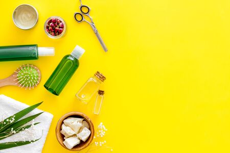 Cosmetics for hair with jojoba, argan or coconut oil in bottle, scissors, brush on yellow background top view mockup