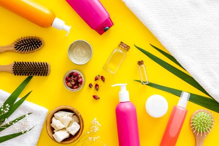 Homemade spa. Cosmetics for hair care with jojoba, argan or coconut oil, comb and shampoo in bottle on yellow background top view pattern