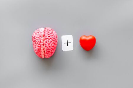 Feelings and mind concept with brain plus heart on gray background top view.
