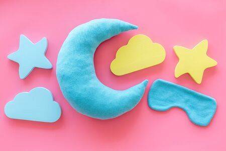 Good dreams. Night sleep concept with moon, clouds, stars toys and blindfold on pink background top view