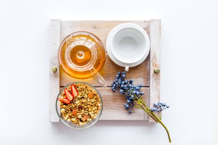 Homemade breakfast in bed with granola, tea and fruit on tray on white wooden background top view