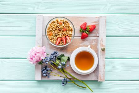 Breakfast in bed with granola, tea and fruit on tray on mint green wooden background top view