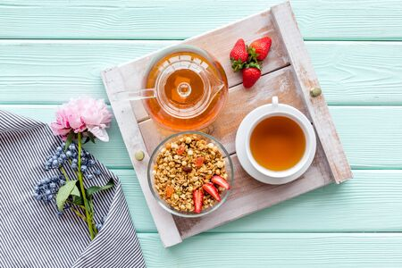 Homemade breakfast in bed with granola, tea and fruit on tray on mint green wooden background top view