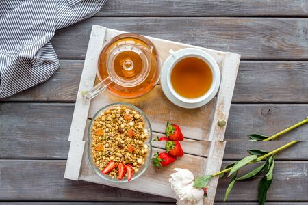 Breakfast in bed with granola, tea and fruit on tray on wooden background top view