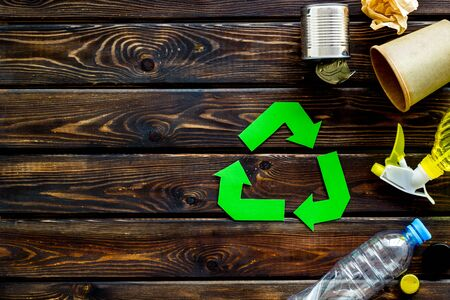 Green recycling symbol with paper cup, plastic bottle, can for ecology on wooden background top view copyspace Stock Photo