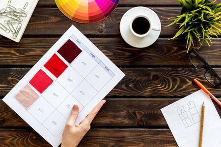 Illustrator-Instrumente. Designer-Arbeitsplatz mit Palette in Händen, Gläsern und Tasse Kaffee auf Draufsicht des hölzernen Hintergrundes