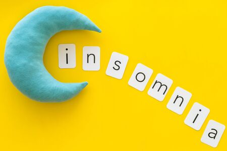 Try to sleep. Insomnia concept with text and moon on yellow background top view