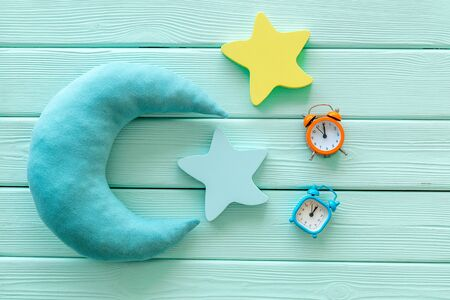 Good dreams. Night sleep concept with moon and clouds toys and alarm clock on mint green wooden background top view Stock Photo