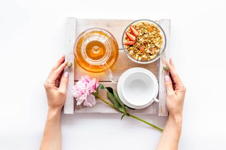 Homemade breakfast in bed with granola, tea and fruit on tray on white background top view