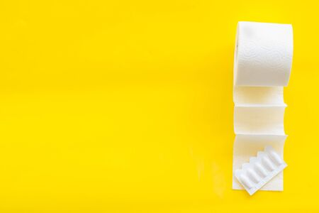 Disease of colon. Proctology concept with toilet paper roll and rectal suppository on yellow background top view space for text Stock Photo