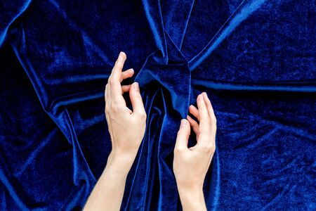 Blue fabric texture and hands background top view