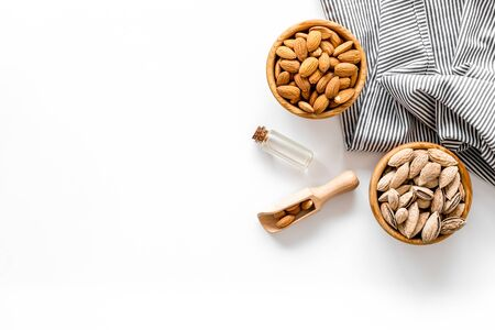 Healthy snack with almonds and oil on white background top view mock up. 写真素材
