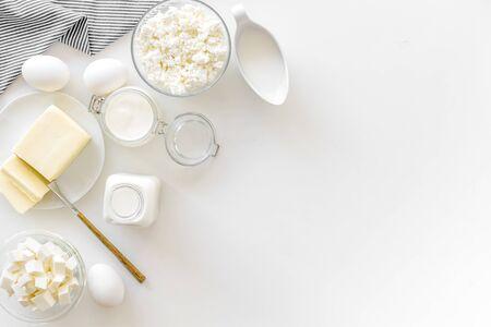 Colazione. Prodotti lattiero-caseari freschi di fattoria con latte, uova, cottage, burro, yogurt su sfondo bianco vista dall'alto mockup Archivio Fotografico