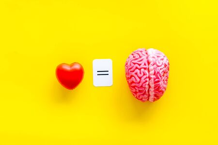 Feelings and mind concept with brain equals to heart on yellow background top view. Stock Photo
