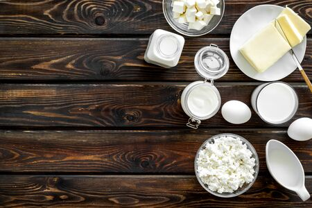 Breakfast on farm with dairy products. Milk, cottage, cheese, yogurt, eggs, butter on wooden background top view space for text