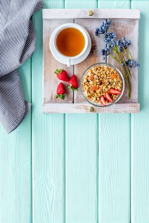 Granola with fruit, cup of tea on tray for breakfast in bed on mint green wooden background top view space for text