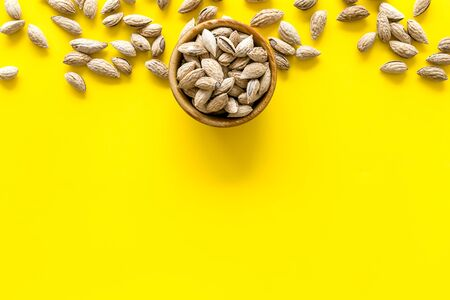 Nuts for snack. Almond on yellow background top view space for text