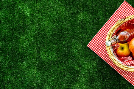 Basket for picnic with apples, drink on green textured background top view copy space