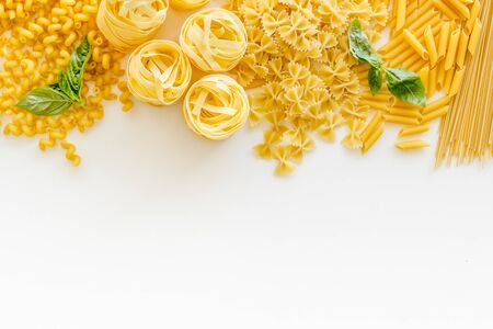 Uncooked pasta for Italian food on white table background top view copyspace.