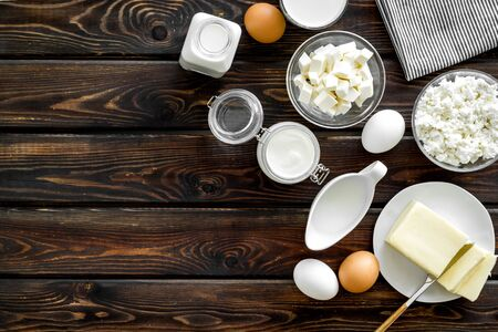 Breakfast. Fresh dairy products from farm with milk, eggs, cottage, butter, yogurt on wooden background top view mockup Stock Photo